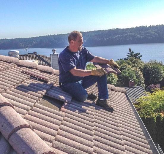 Dan Koesterman of Rooftop Services, LLC on a tile roof performing repairs